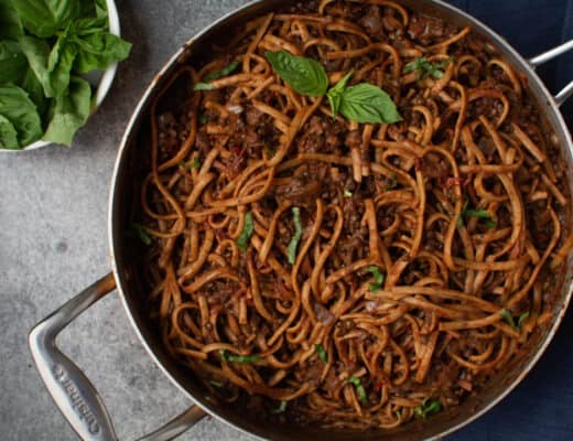 lentil bolognese and noodles in pan next to a bowl of fresh basil