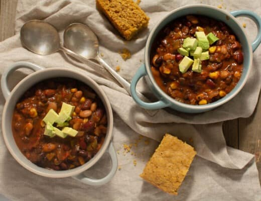 Birdseye view of two bowls of chili topped with avocado and a side of cornbread.